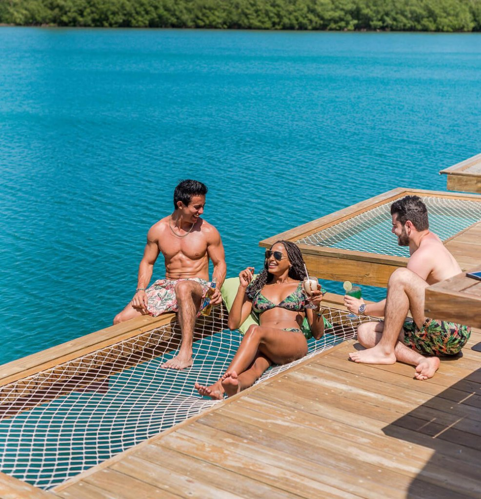 Three friends in swimsuits on a pier | Design your custom swimsuit